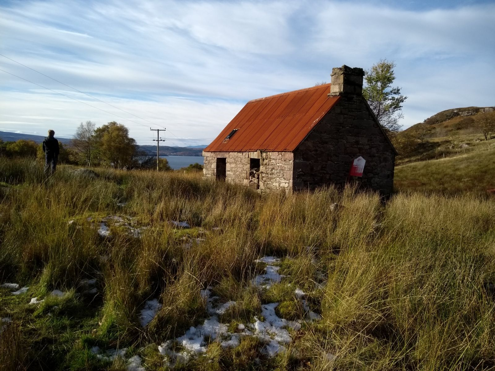 Old building in the highlands, tall grass, man on hill